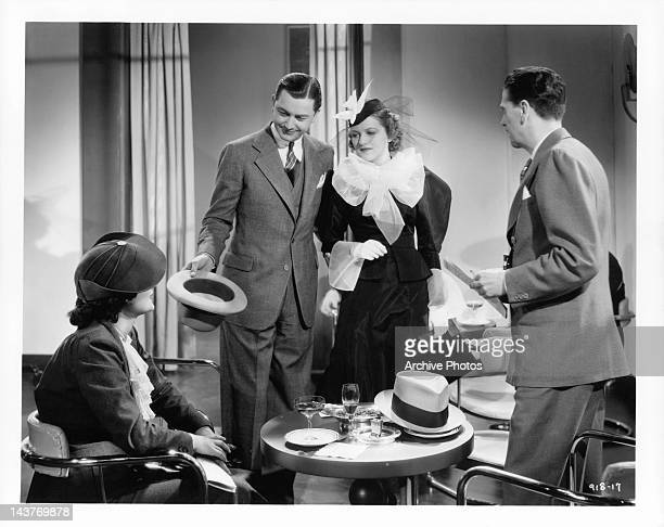 Robert Young and Betty Furness talking to woman and man at table in a scene from the film 'The Three Wise Guys', 1936.