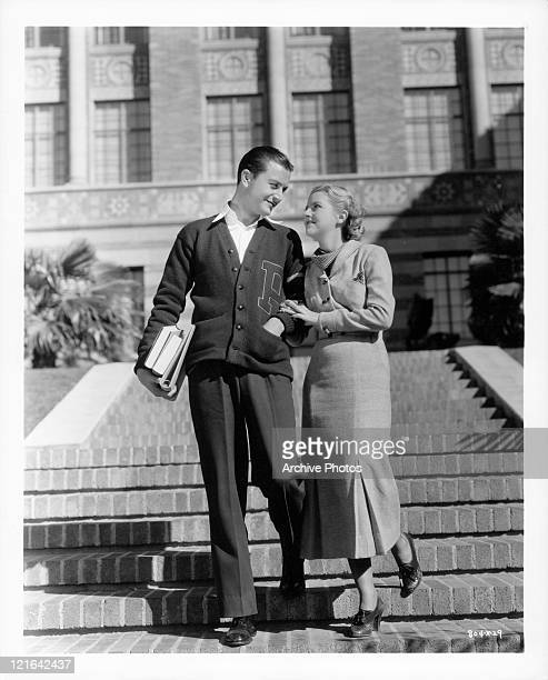Robert Young and Betty Furness walking down the steps in a scene from the film 'The Band Played On', 1934.