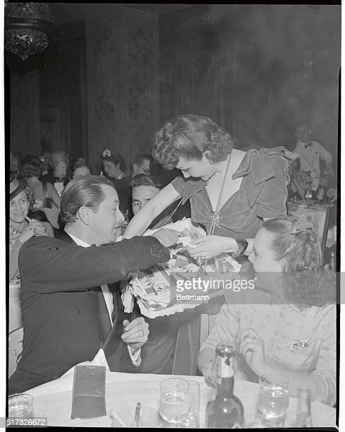 Robert Young movie actor does his bit for FrancoBritish war relief by buying cigarettes from Claudette Colbert film star at party staged here recently