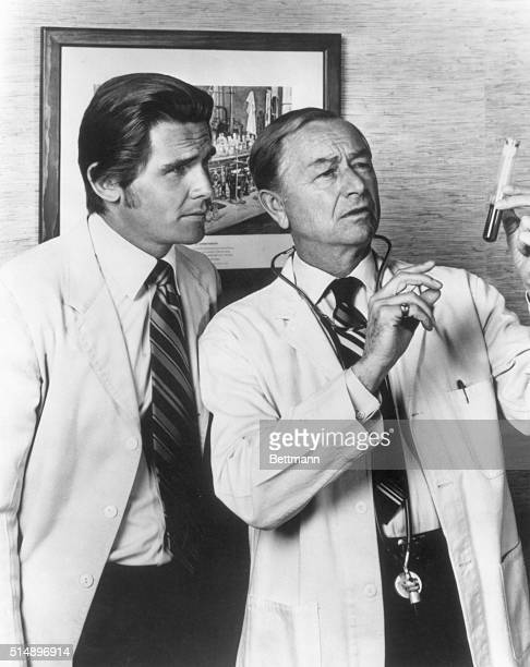 Robert Young shown here with a colleague looking at a test tube stars as Dr Marcus Welby compassionate family practitioner and knowledgeable head of...