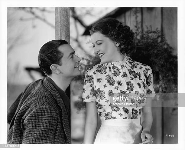 Robert Young smiling as he looks at Betty Furness in a scene from the film 'The Three Wise Guys', 1936.