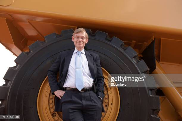 Robert Zoellick former president of the World Bank Group poses for a photograph in front of a Caterpillar Inc loader on display at the annual Diggers...