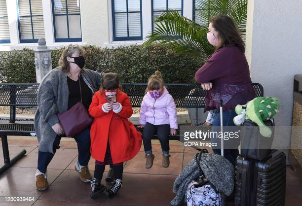 Roberta Davis and her family wear face masks while waiting for a train at the Orlando Amtrak station on the first day that the Transportation...