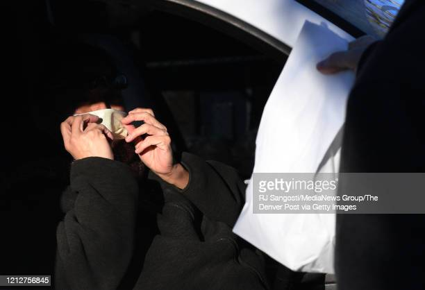 Roberta Luna picks up free meals, for her three grandchildren, outside Cowell Elementary on March 16, 2020 in Denver, Colorado. Denver Public Schools...