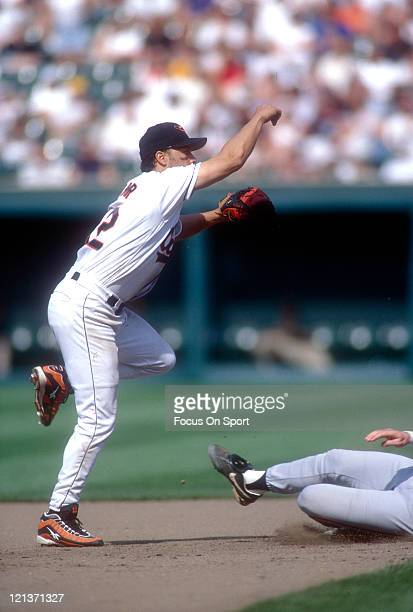 Roberto Alomar of the Baltimore Orioles gets his throw off to complete the double play during an Major League Baseball game circa 1996 at Oriole Park...