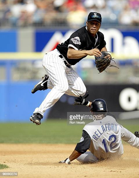 Roberto Alomar of the Chicago White Sox leaps into the air at second base after a throw during an MLB game against the Kansas City Royals at Comiskey...