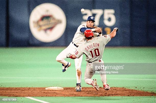 Roberto Alomar of the Toronto Blue Jays attempts to turn a double play against Darren Daulton of the Philadelphia Phillies during a 1993 World Series...