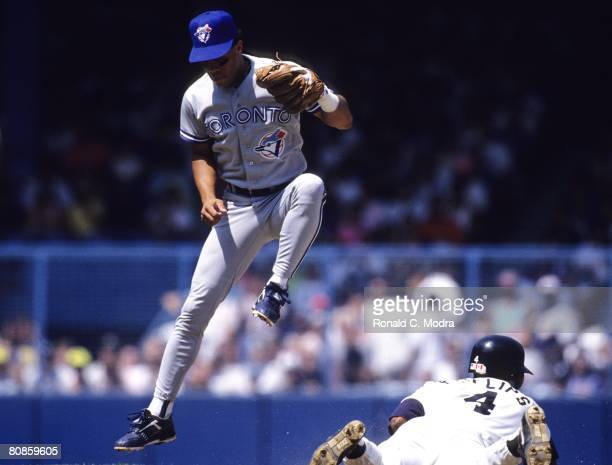 Roberto Alomar of the Toronto Blue Jays jumps over a sliding Tony Phillips of the Detroit Tigers on August 18 1991 in Detroit Michigan