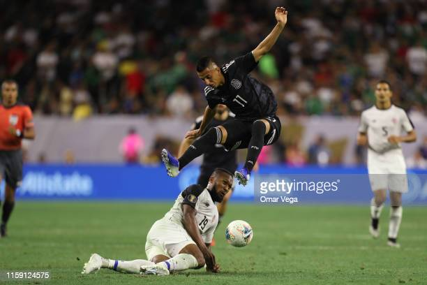 Roberto Alvarado of Mexico and Kendall Waston of Costa Rica fight for the ball during a quarterfinal match between Mexico and Costa Rica as part of...