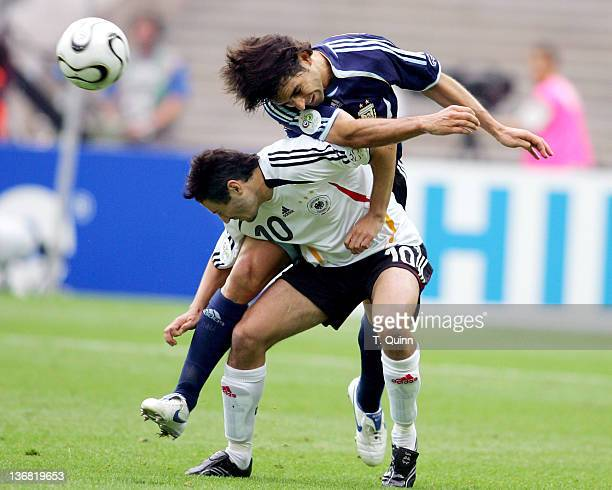 Roberto Ayala of Argentina heads over the back of Oliver Neuville of Germany during their quarterfinal match at the Olympiastadion in Berlin Germany...