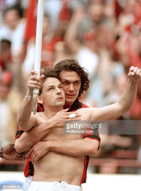 Roberto Baggio of AC Milan celebrates with teammate Paolo Maldini while holding a corner flag during the Serie A match between AC Milan and...