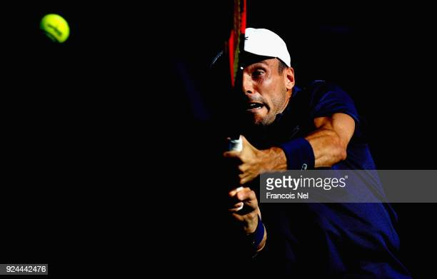 Roberto Bautista Agut of Spain plays a backhand in his match against Florian Mayer of Germany during day one of the ATP Dubai Duty Free Tennis...