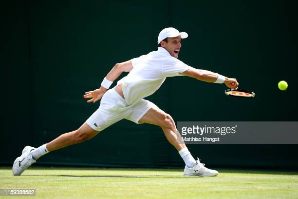 Roberto Bautista Agut of Spain plays a backhand in his Men's Singles first round match against Peter Gojowczyk of Germany during Day one of The...