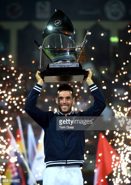 Roberto Bautista Agut of Spain poses with the trophy after winning the final match against Lucas Pouille of France on day six of the ATP Dubai Duty...