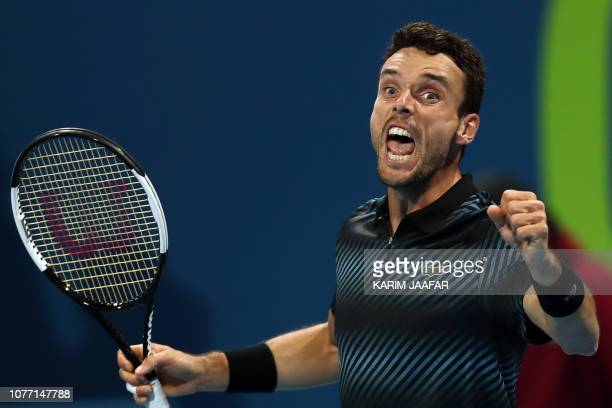 TOPSHOT Roberto Bautista Agut of Spain reacts after defeating Novak Djokovic of Serbia in their ATP Qatar Open tennis semifinal match in Doha on...