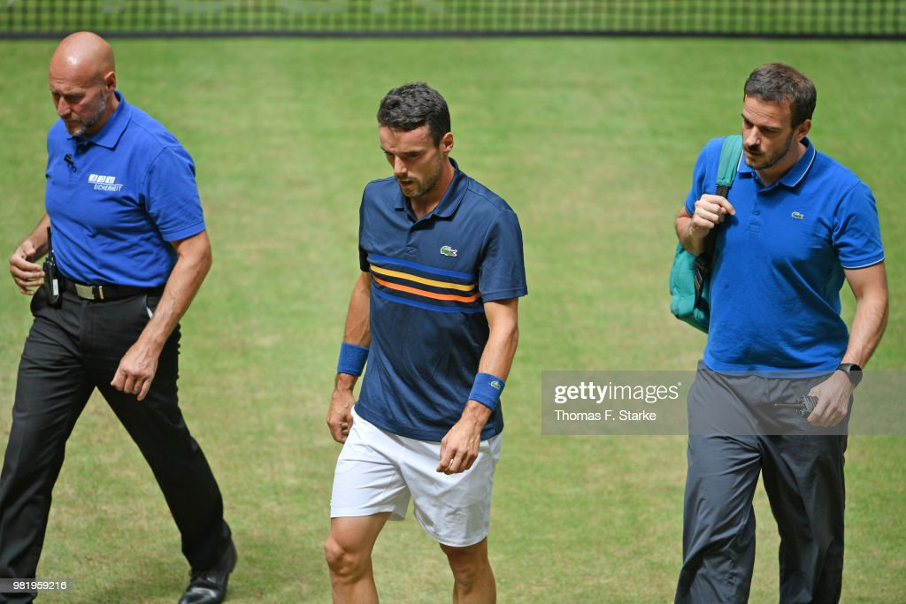 Roberto Bautista Agut (M) of Spain reacts leaves the pitch after picking up an injury in his half final match against Borna Coric of Croatia during day six of the Gerry Weber Open at Gerry Weber Stadium on June 23, 2018 in Halle, Germany.