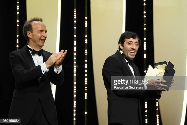 Roberto Benigni L stands by as actor Marcello Fonte receives the Best Actor award for his role in 'Dogman' on stage during the Closing Ceremony at...