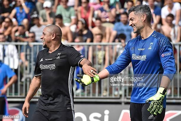 Roberto Carlos of AC Milan Inter Legends greets Vitor Baia of World AllStars during the Ultimate Champions Match between Milan Inter Legends and...
