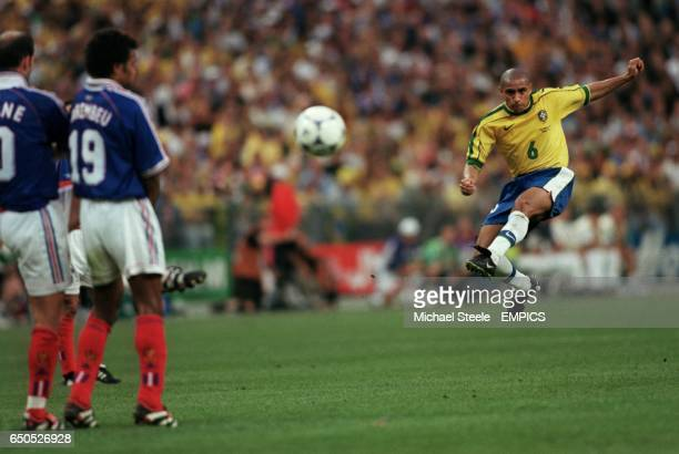 Roberto Carlos of Brazil tries to curl a freekick around the France wall