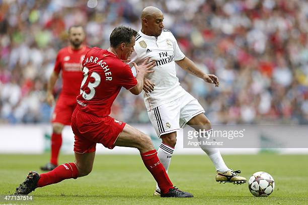 Roberto Carlos of Real Madrid Leyendas competes for the ball with Jamie Carragher of Liverpool Legends during the Corazon Classic charity match...