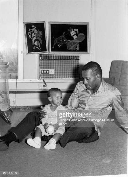 Roberto Clemente and his son Roberto Clemente Jr seated on floor in their apartment in East Liberty Pittsburgh Pennsylvania June 1966