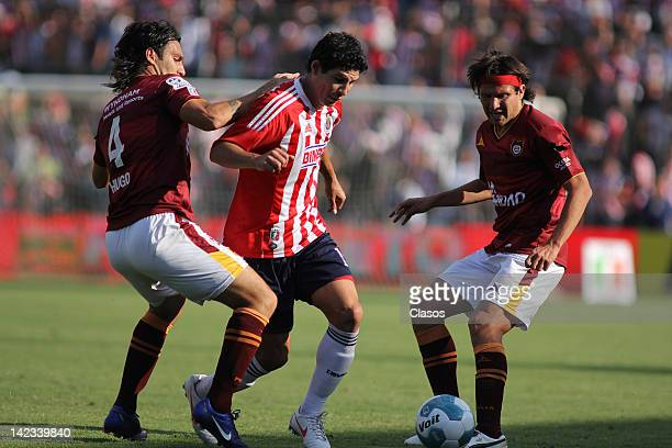 Roberto Colace of Estudiantes, Jonny Magallon of Chivas and Gabriel Pereyra of Chivas struggles for the ball during a match between Estudiantes v...