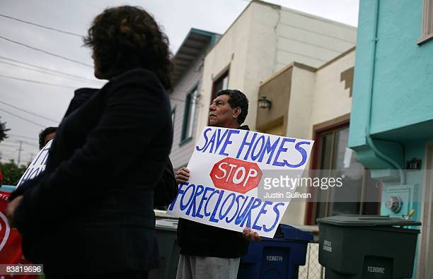 Roberto Colocho holds a sign during a press conference about home foreclosures November 25, 2008 in South San Francisco, California. Community...