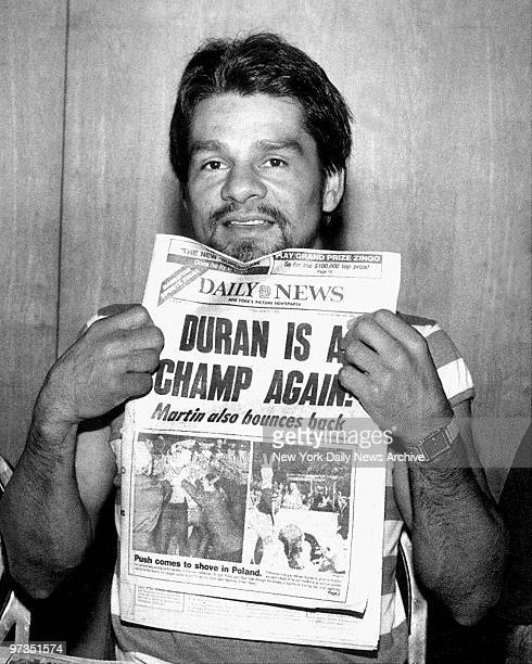 Roberto Duran shows Daily News front page headline announcing he has regained his boxing title
