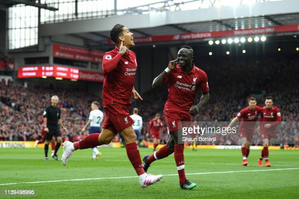 Roberto Firminho of Liverpool celebrates with Saido Mane after he scores his sides first goal during the Premier League match between Liverpool FC...