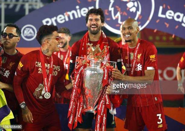 Roberto Firmino Alisson Becker and Fabinho of Liverpool celebrate with The Premier League trophy following the Premier League match between Liverpool...
