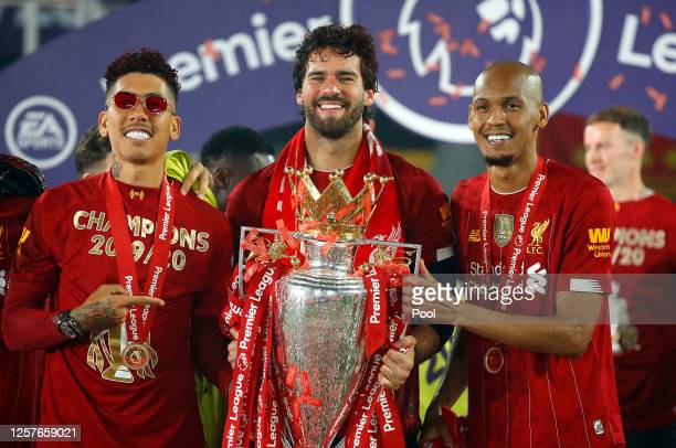Roberto Firmino, Alisson Becker and Fabinho of Liverpool celebrate with The Premier League trophy following the Premier League match between...