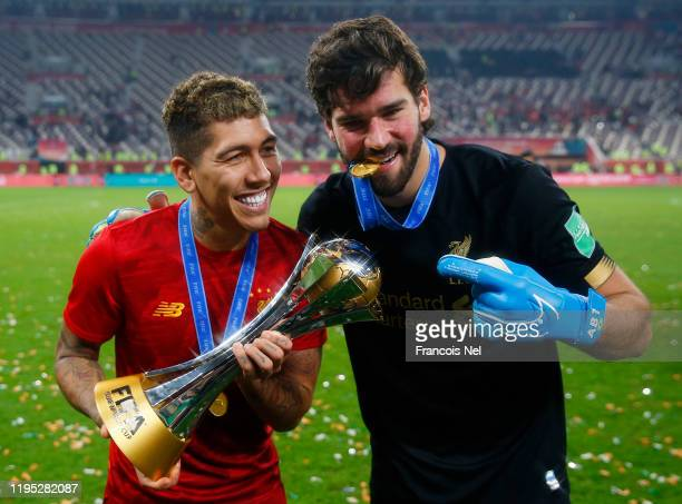 Roberto Firmino and Alisson Becker of Liverpool pose with the FIFA Club World Cup trophy following their victory in the FIFA Club World Cup Qatar...