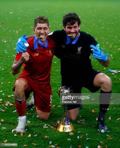 Roberto Firmino and Alisson Becker of Liverpool pose with the FIFA Club World Cup trophy following their victory FIFA Club World Cup Qatar 2019 Final...