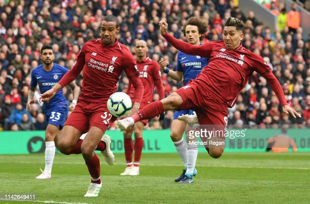 Roberto Firmino and Joel Matip of Liverpool stretch fpr the ball during the Premier League match between Liverpool FC and Chelsea FC at Anfield on...