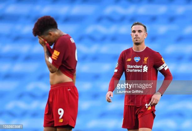 Roberto Firmino and Jordan Henderson of Liverpool react to Manchester City scoring there third goal of the game during the Premier League match...