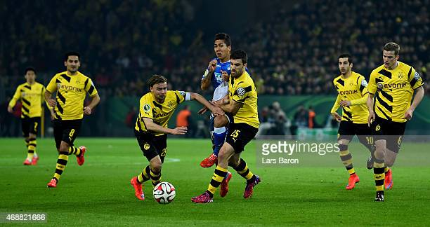 Roberto Firmino of 1899 Hoffenheim is challenged by Marcel Schmelzer of Borussia Dortmund and Sokratis Papastathopoulos of Borussia Dortmund during...