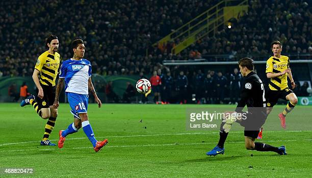 Roberto Firmino of 1899 Hoffenheim scores his teams second goal past goalkeeper Mitchell Langerak of Borussia Dortmund during the DFB Cup Quarter...