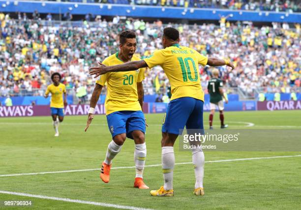 Roberto Firmino of Brazil celebrates with team mate Neymar Jr after scoring his team's second goal during the 2018 FIFA World Cup Russia Round of 16...