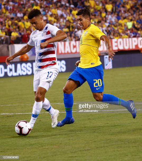 Roberto Firmino of Brazil chases Antonee Robinson of the USA during their friendly match at MetLife Stadium on September 7 2018 in East Rutherford...