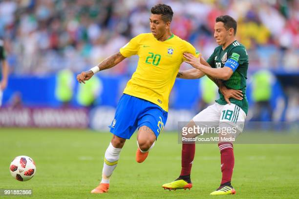 Roberto Firmino of Brazil competes with Andres Guardado of Mexico during the 2018 FIFA World Cup Russia Round of 16 match between Brazil and Mexico...