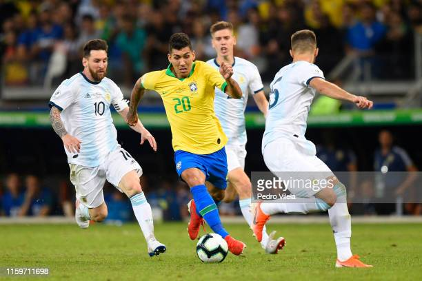 Roberto Firmino of Brazil controls the ball against Lionel Messi of Argentina during the Copa America Brazil 2019 Semi Final match between Brazil and...
