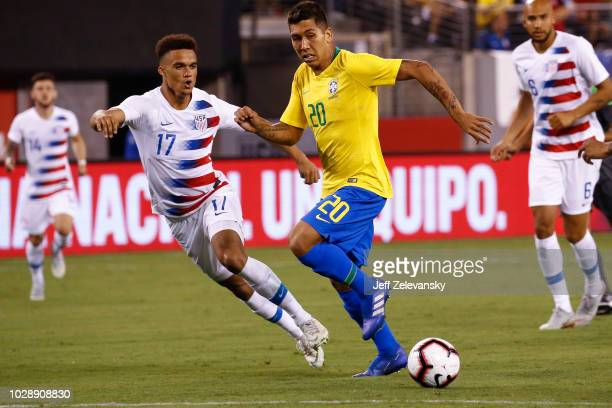 Roberto Firmino of Brazil drives by Antonee Robinson of the USA during their friendly match at MetLife Stadium on September 7 2018 in East Rutherford...