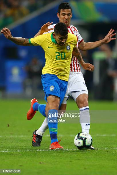 Roberto Firmino of Brazil fights for the ball with Fabian Balbuena of Paraguay during the Copa America Brazil 2019 quarterfinal match between Brazil...