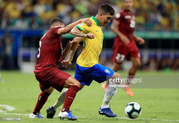 Roberto Firmino of Brazil fights for the ball with Tomas Rincon of Venezuela during the Copa America Brazil 2019 group A match between Brazil and...