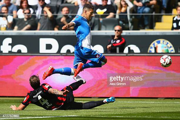 Roberto Firmino of Hoffenheim is challenged by Marco Russ of Frankfurt during the Bundesliga match between Eintracht Frankfurt and 1899 Hoffenheim at...