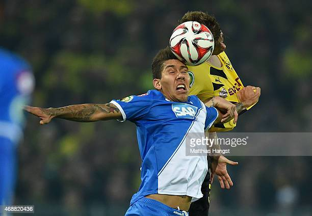 Roberto Firmino of Hoffenheim jumps for a header with Erik Durm of Dortmund during the DFB Cup Quarter Final match between Borussia Dortmund and 1899...