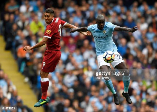 Roberto Firmino of Liverpool and Benjamin Mendy of Manchester City battle for possession during the Premier League match between Manchester City and...