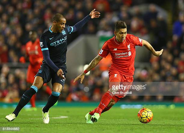 Roberto Firmino of Liverpool and Fernando of Manchester City in action during the Barclays Premier League match between Liverpool and Manchester City...