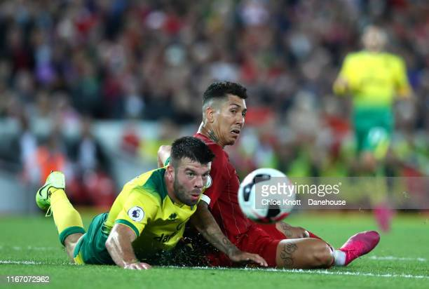 Roberto Firmino of Liverpool and Grant Hanley of Norwich City in action during the Premier League match between Liverpool FC and Norwich City at...