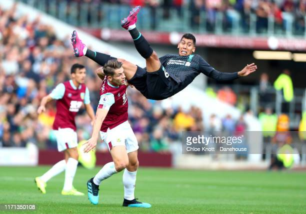 Roberto Firmino of Liverpool and James Tarowski of Burnley FC in action during the Premier League match between Burnley FC and Liverpool FC at Turf...